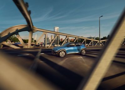 The new Hyundai Kona in Surfy Blue from the side driving over a bridge.